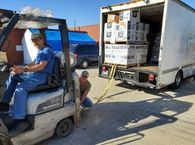 Good News Mission helps us unload our truck of Donations from Midwest Foods